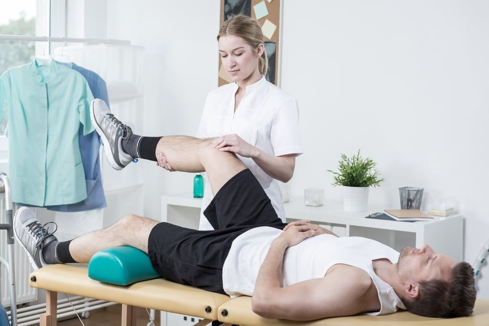 Horizontal view of female chiropractor exercising man's leg