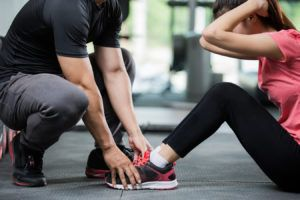 Trainer holding a woman in the leg exercise by Sit-up