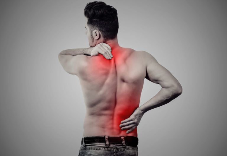 Young man with lower and upper back pain