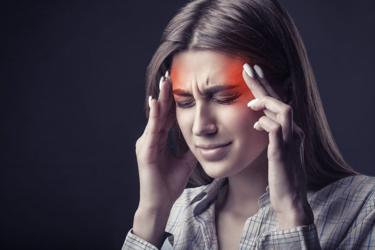 Young woman is suffering from a headache against a dark background